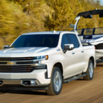 White Silverado towing a boat