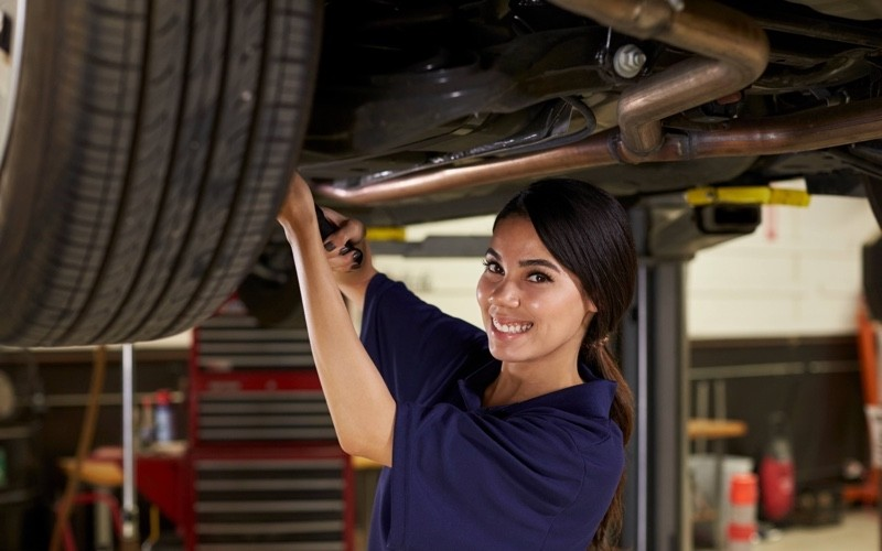 Female Auto Mechanic Working Under Car