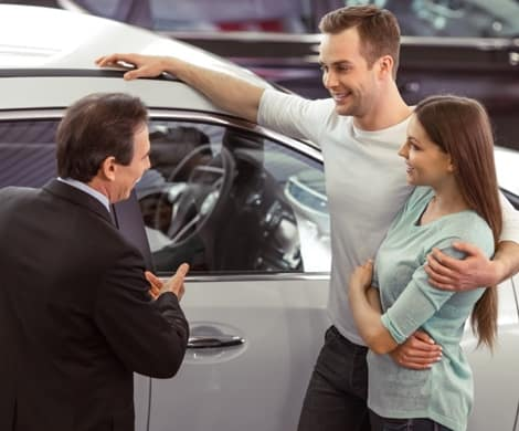 salesman helping a couple looking for a vehicle