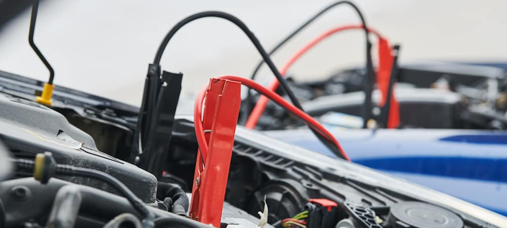 Red and black jumper cables attached to a car's battery terminal