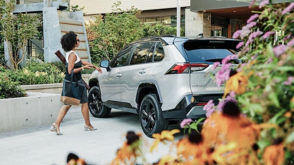 Woman reaching for door of Toyota RAV4