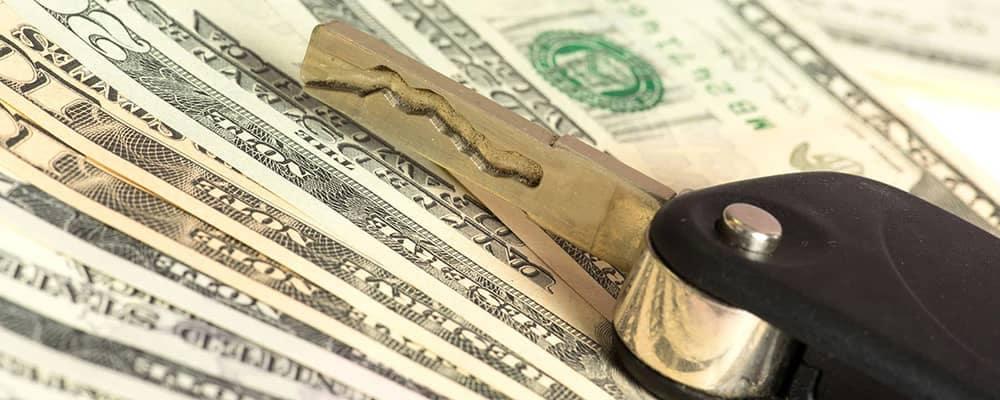 Money with car keys representing loan