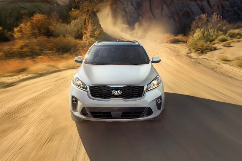 Front view of a Gray Kia Sorento driving on a dusty road