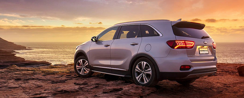 Gray Kia sorento parked on a rocky beach at sunset