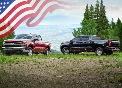 Two Chevy Silverados in an open field with an American Flag