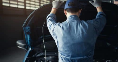 Person inspecting under the hood of vehicle