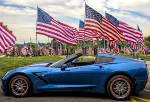 A blue Corvette and lots of flags