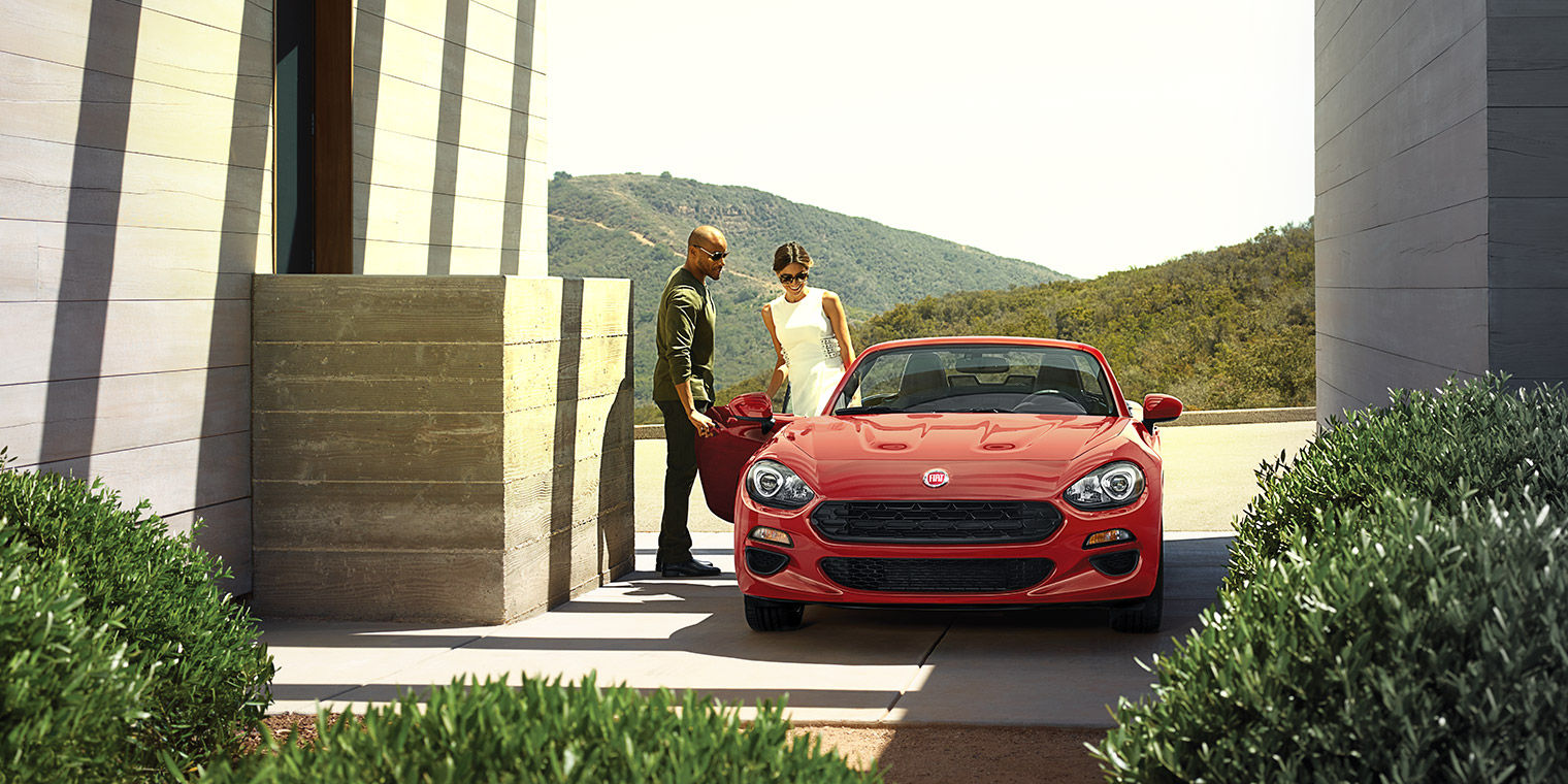 Man Helping Women into Red FIAT Spider