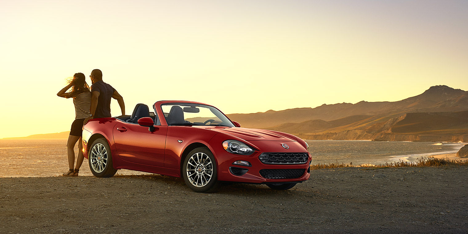 Two People Look Into the Distance as They Lean Against Parked Red FIAT Spider