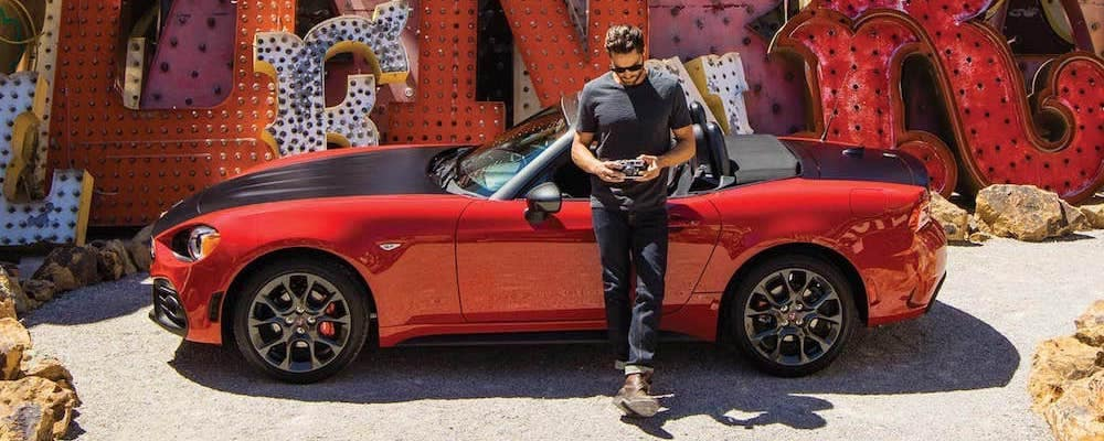 man with camera standing beside red and black 2019 fiat 124 spider