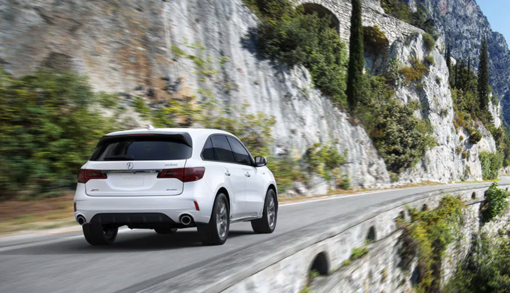 white acura driving cliffside