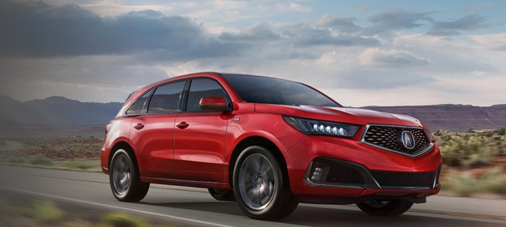 Red 2020 Acura MDX driving in the country