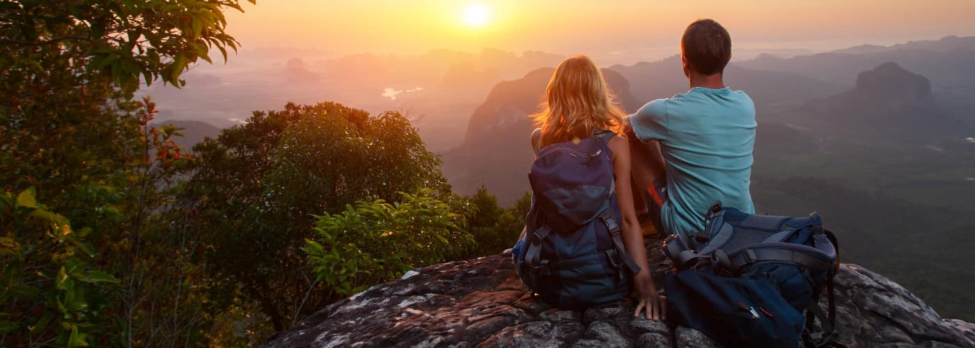 couple on cliff watching the sunset