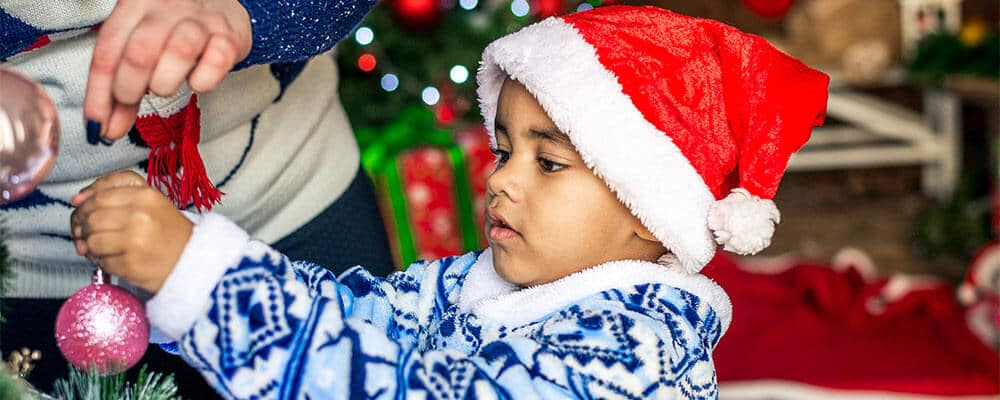Young boy in Santa hat helping with Christmas decorations