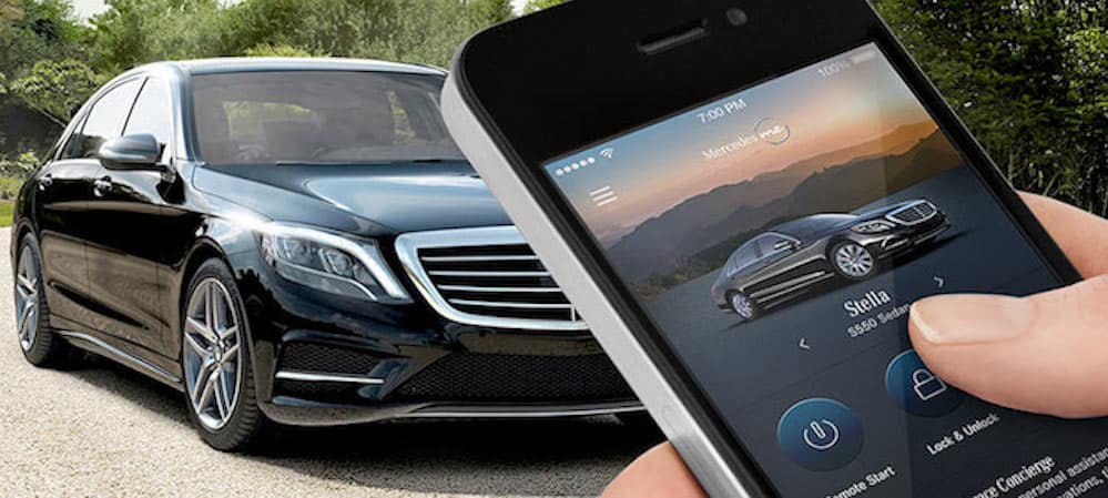 Person holding smartphone with Mercedes me app pulled up while facing a Mercedes-Benz vehicle