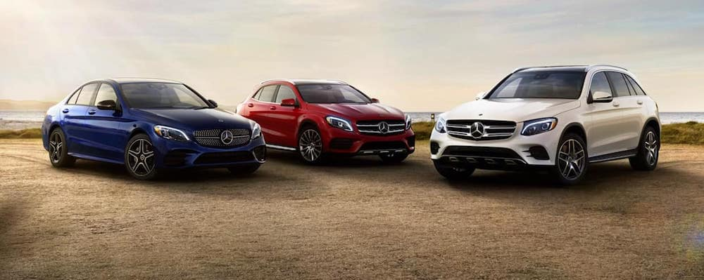 Three Mercedes-Benz vehicles parked angled towards one another in the desert