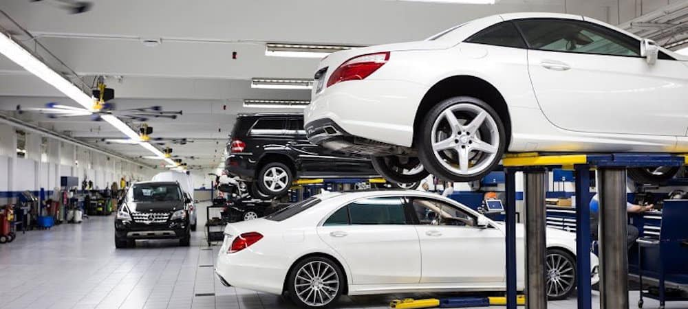 Service bay with white Mercedes-Benz on lift in foreground