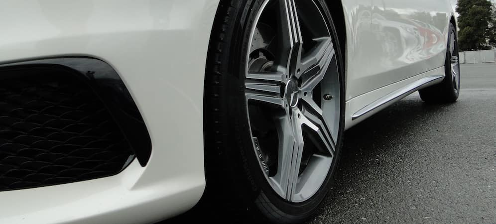 Closeup of front driver side tire on a white Mercedes-Benz