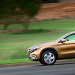 Copper Mercedes-Benz SUV driving on country highway