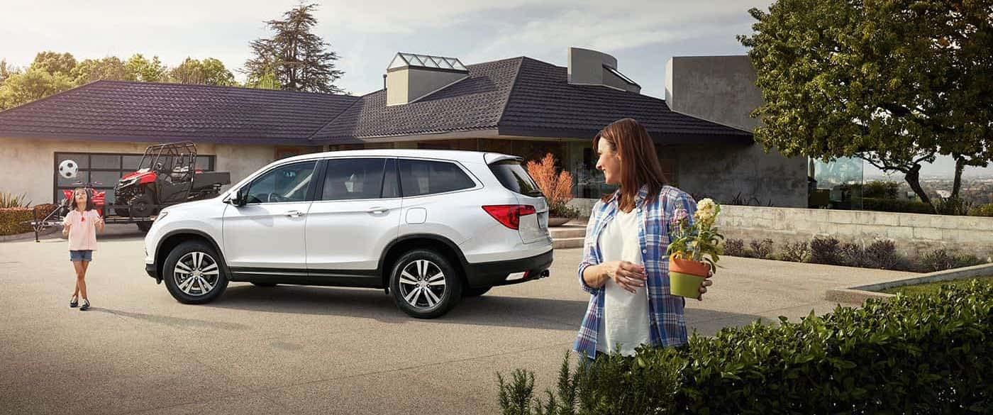 Honda Pilot parked in front of home with family outside