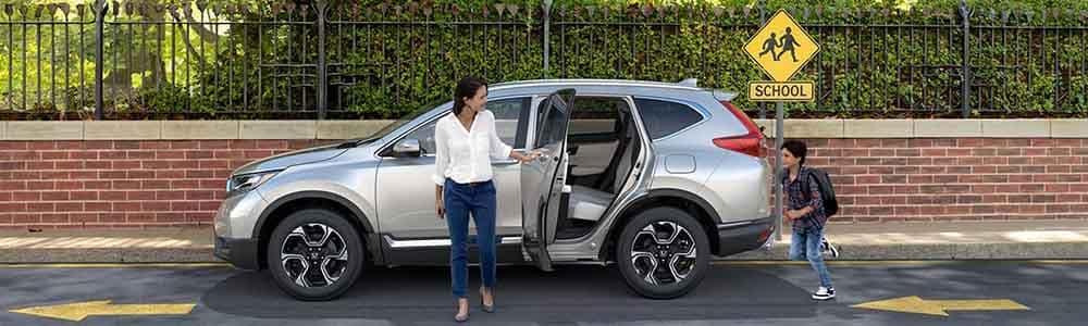 Mom holding holding door of a 2018 Honda CR-V open for child in school pickup line