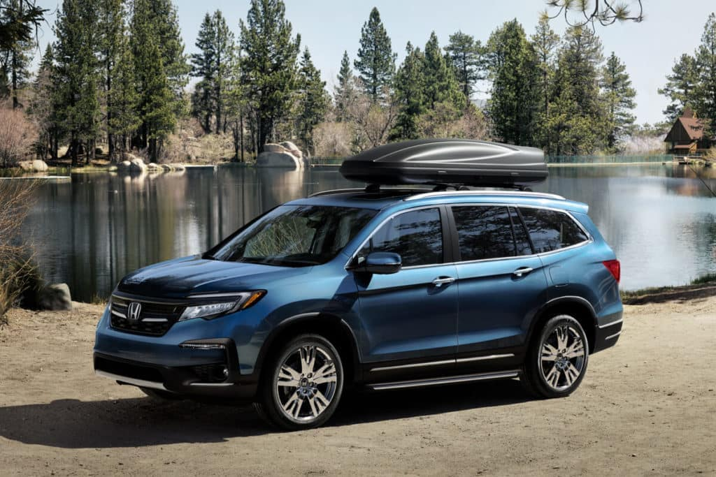 Blue 2021 Honda Pilot with roof box in front of lake