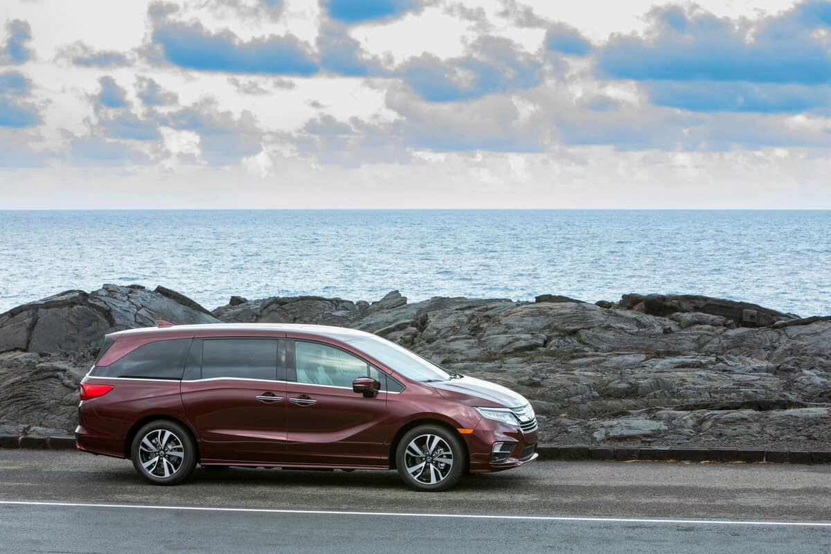 Red 2020 Honda Odyssey driving by the sea