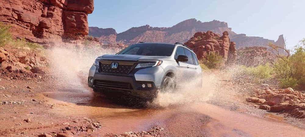 Silver AWD 2020 Honda Passport driving through puddle int he desert