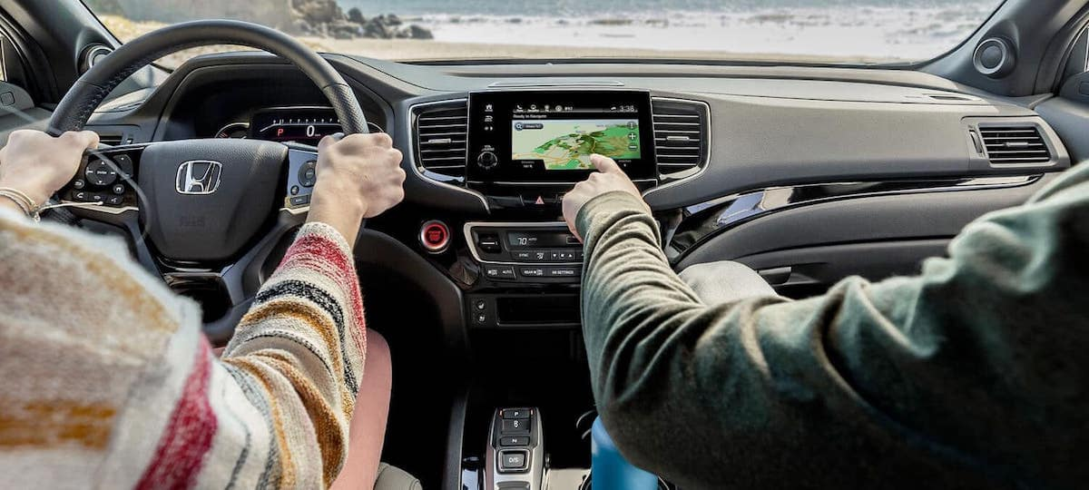 People sitting in front seats of 2020 Honda Passport AWD and using touchscreen navigation system
