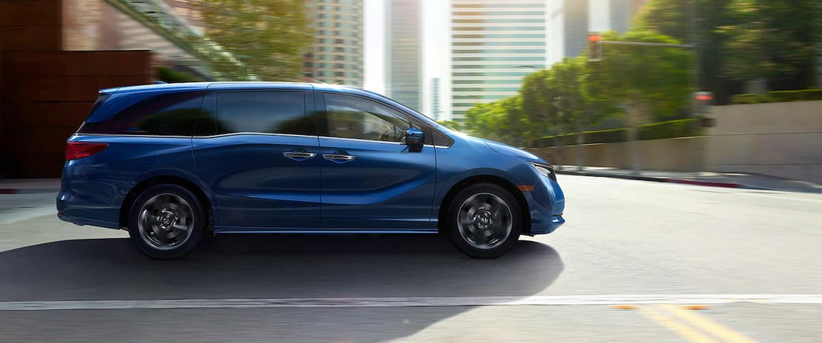 Side view of blue 2021 Honda Odyssey driving through city