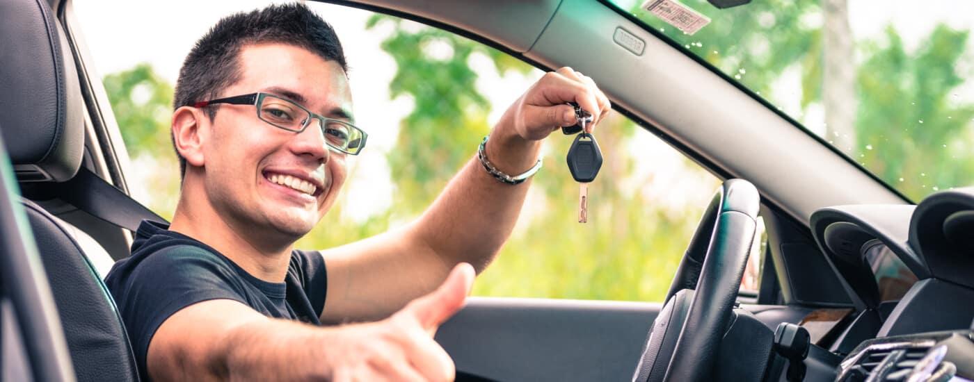 Man holding car keys giving thumbs up