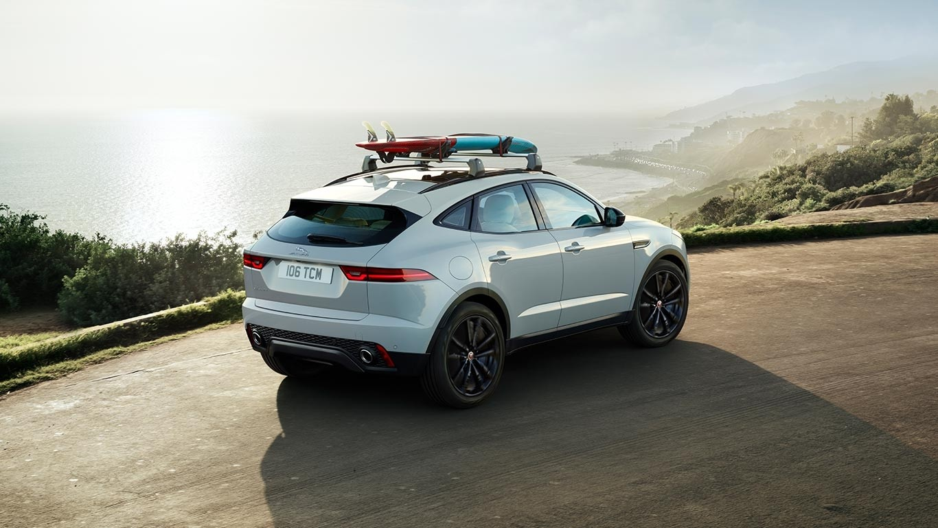 2018 Jaguar E-PACE driving near beach with surf board attached on top rails