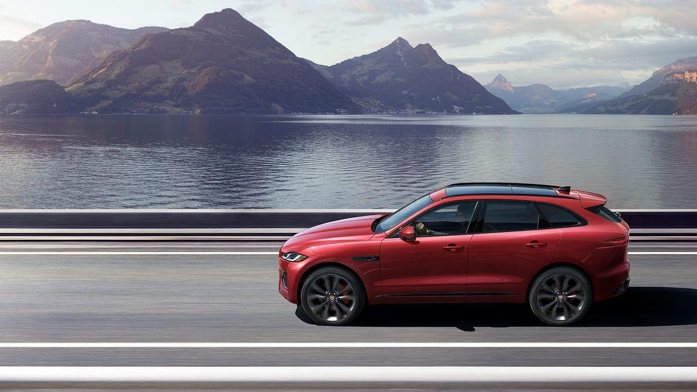 The 2021 Jaguar F-Pace driving in front of water and mountains.