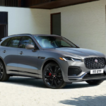 The 2021 Jaguar F-Pace parked out front of a house with a couple next to it.