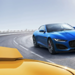 Two Jaguar F-Type vehicles racing on a track.