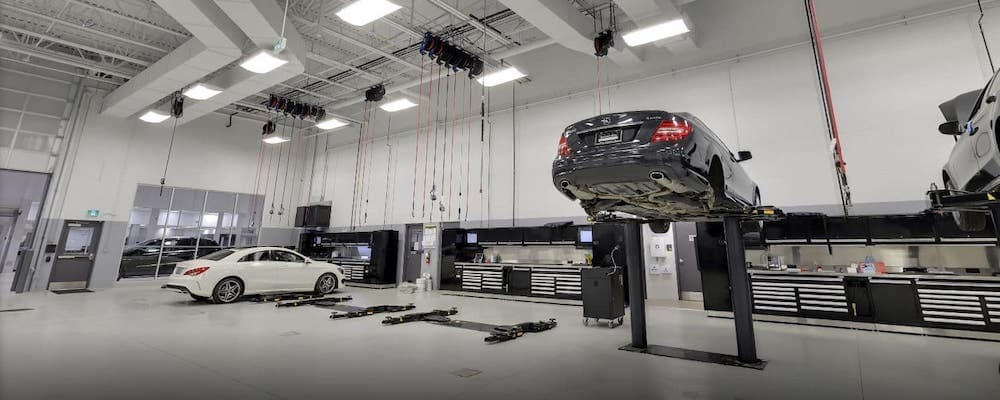 Mercedes-Benz service bay with lifted black sedan and white sedan