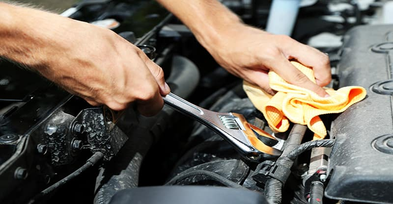 man holding wrench working on car engine