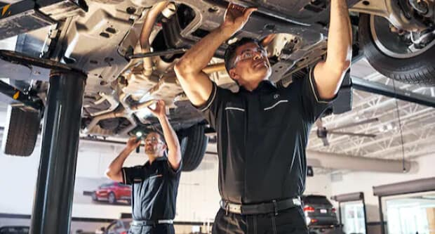 Service techs under Mercedes-Benz vehicles