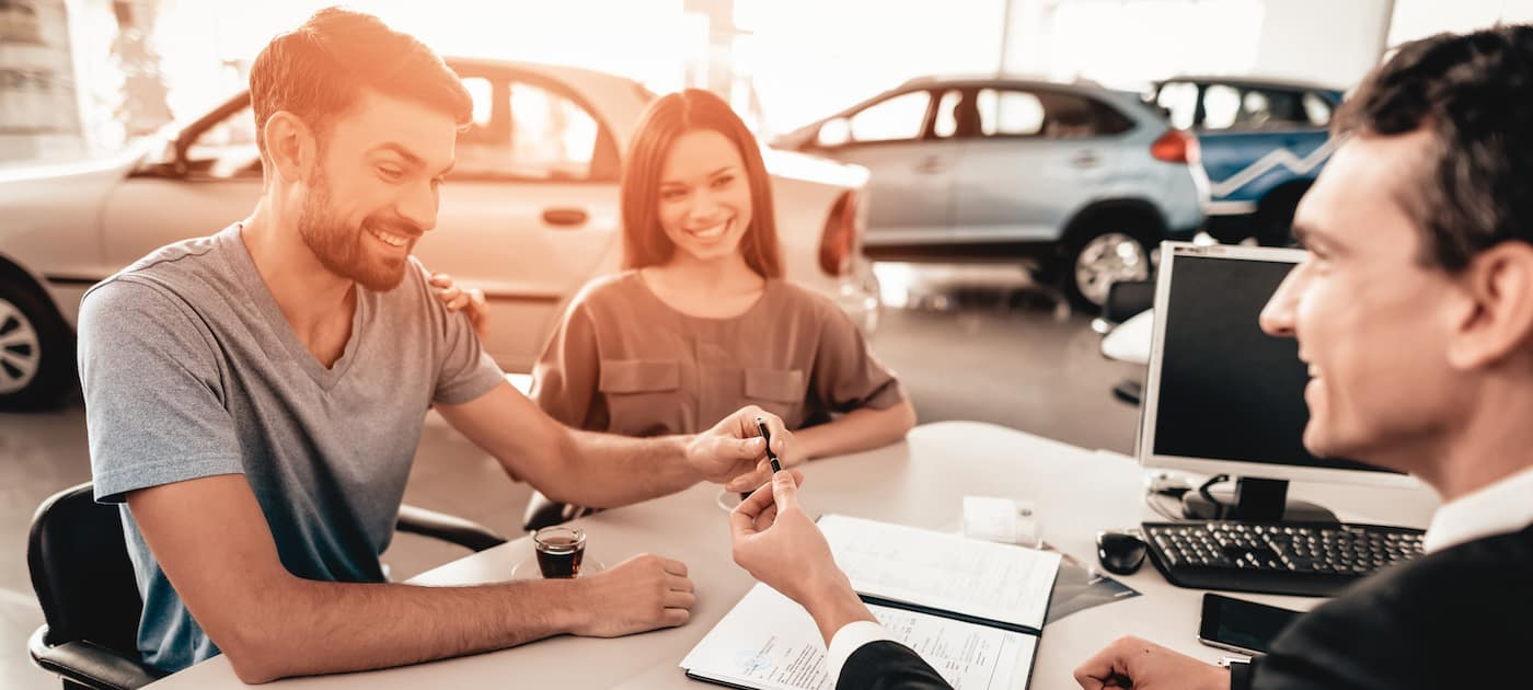 Young Family Are Signing A Contract To Buy A Car.