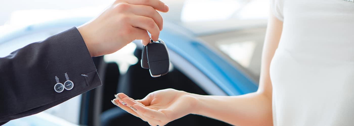 car salesman handing a woman the keys to a new car