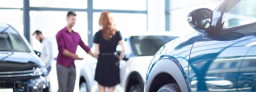 Customers review vehicles in a new car showroom