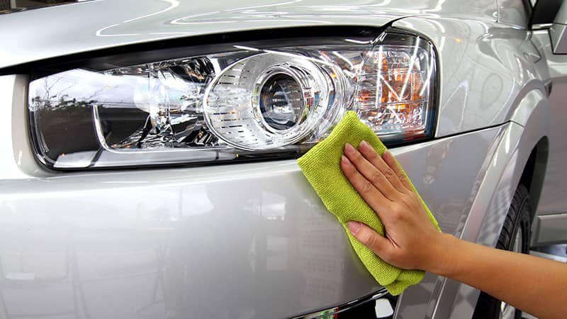 Hand polishing a headlight on a car