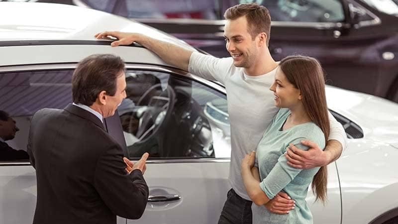 Couple talking to salesman about a car