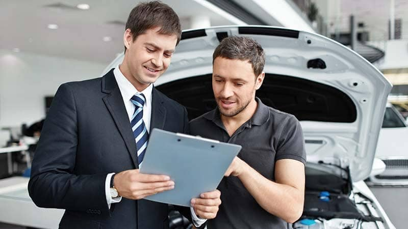 Salesman showing a customer his car report