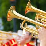 gold trumpets playing in marching band with red and gold uniforms