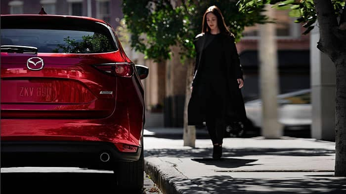 Woman walking to a 2018 Mazda CX-5 Parked on Side of Road