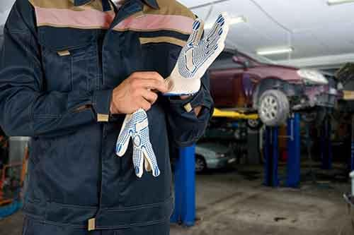 Auto mechanic putting on work gloves