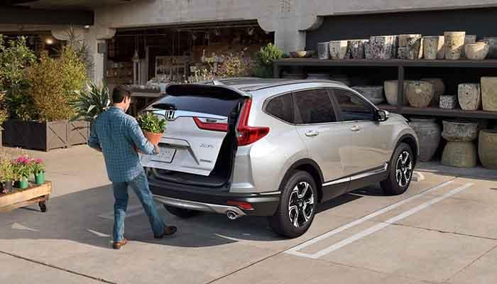 Man opening tailgate of 2018 Honda CR-V by waving foot under sensor