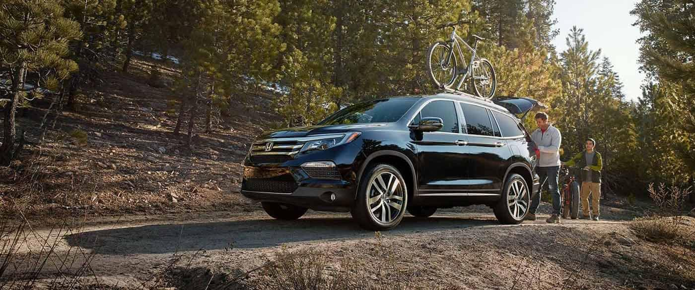 Honda Pilot parked at forest with bikes on bike rack