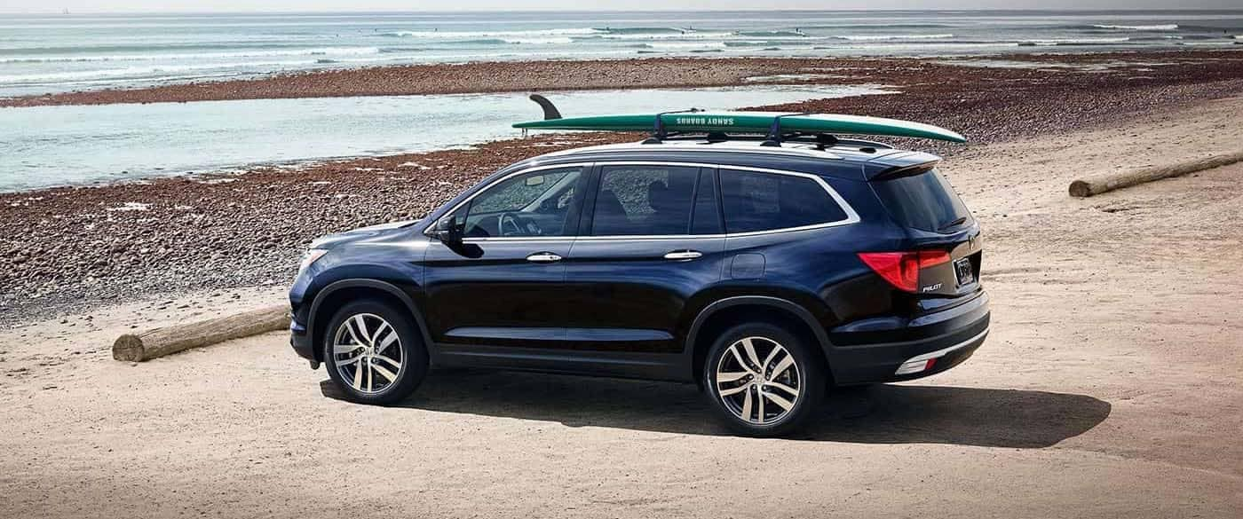 2018 Honda Pilot with Surf Board hooked on roof railes parked at the ocean